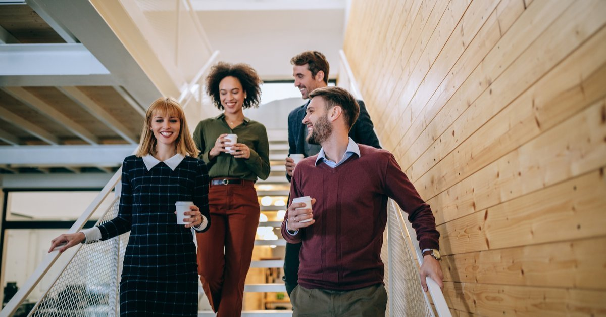 Four young professional men and women walking down steps with coffee, smiling