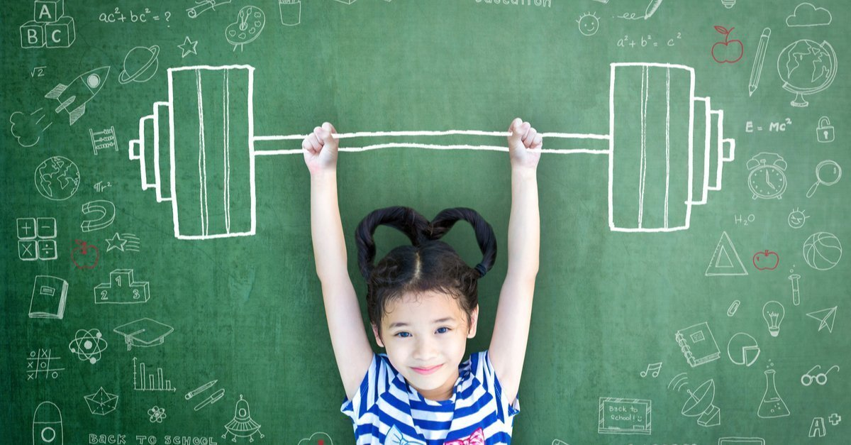 Young girl holding up chalk drawn dumb bells in front of chalk board