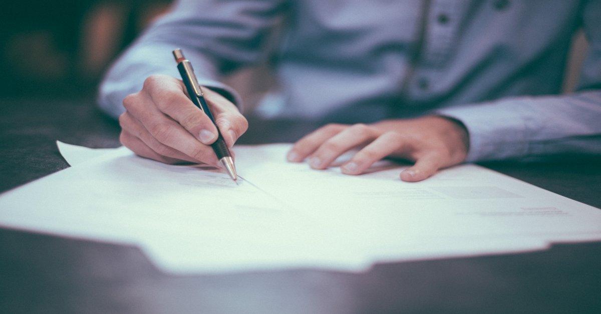 Person writing CV at desk