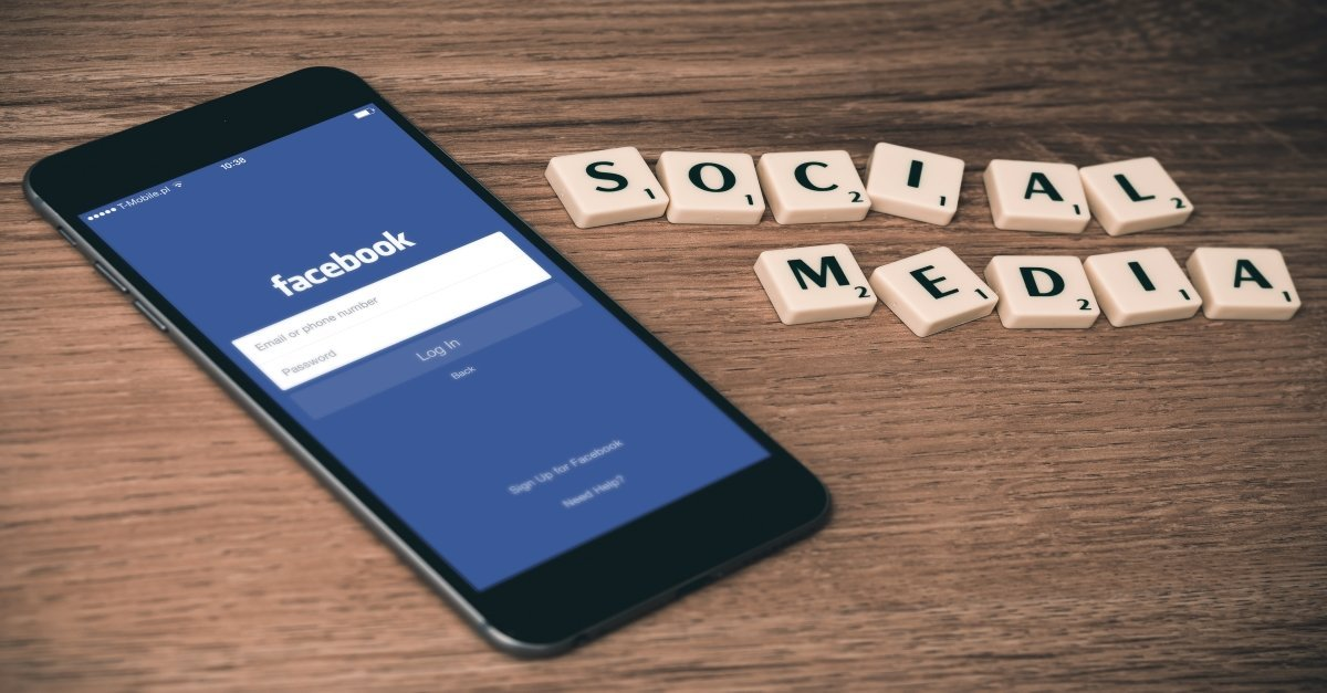 'social media' spelt out in scrappbel words next to iPhone with Facebook login page