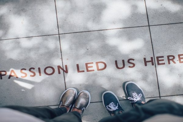 pair of feet behind wording on pavement spelling 'passion led us here'