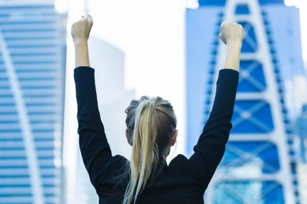Woman facing back looking at high rise buildings, holding fists up
