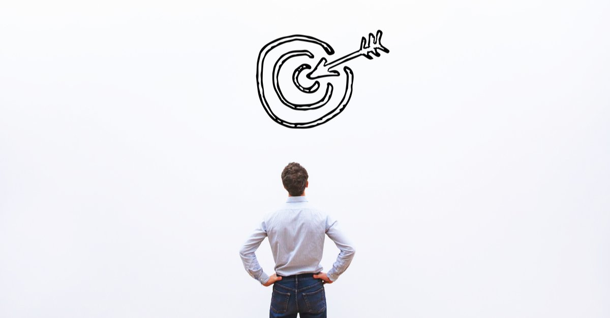 Back of a man staring at a drawn bulls eye with arrow in centre