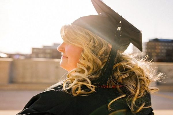 Middle aged womn wearing mortarboard smiling looking to left