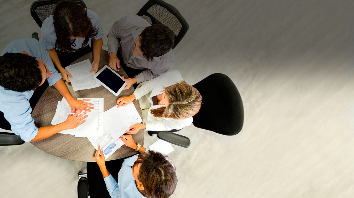 Professionals sitting round small desk aerial view
