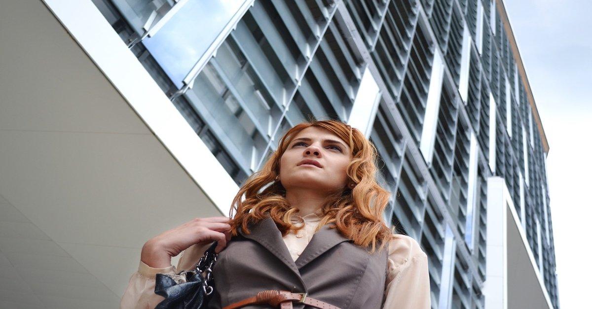Business woman looking ahead seen from below, building behind