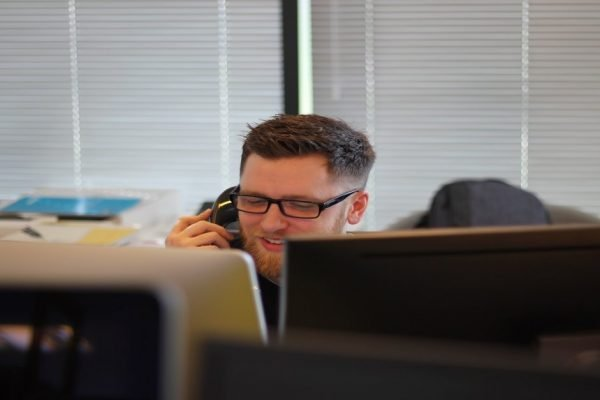 Man peeping over computers, talking on phone