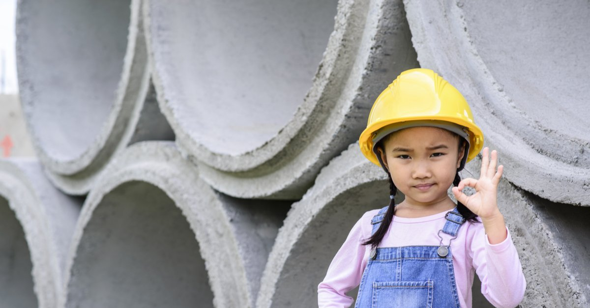 Young female child in builders hat looking confident