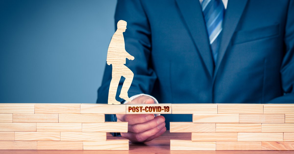 Business man creating building blocks for wooden man to step on with stamp saying 'Covid19'