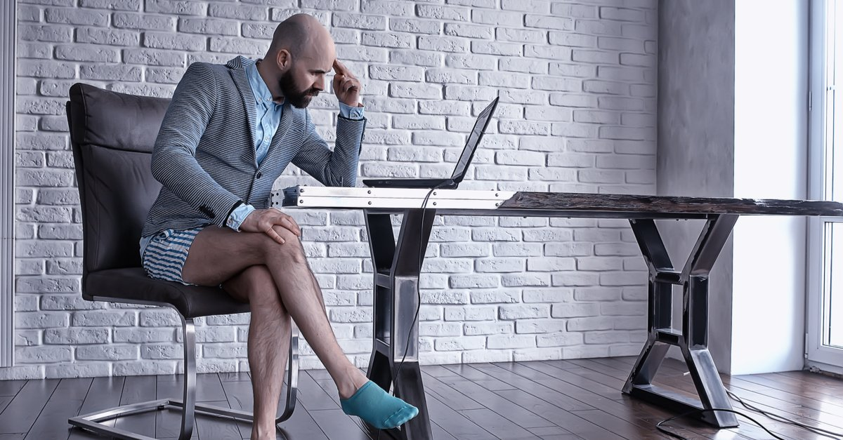 man at desk with half a sti on, no trousers, looking at his laptop