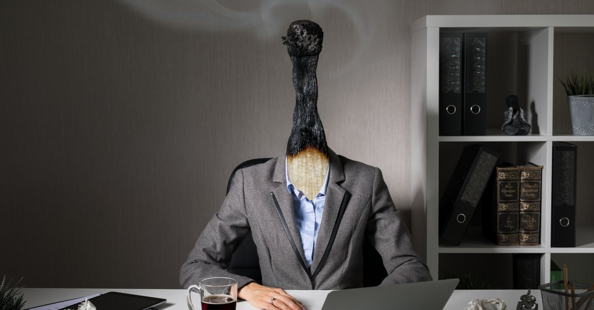 Professiinal at desk with head as a burnt out match