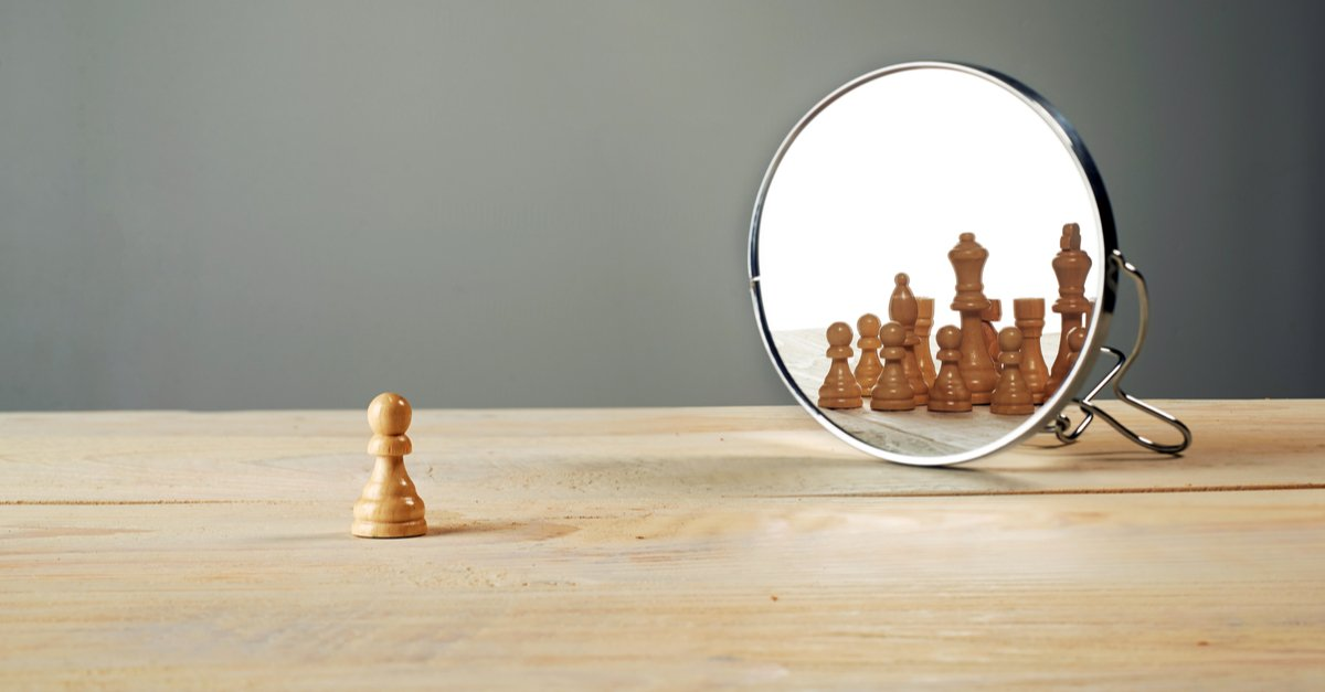 Chess pawn starting in mirror reflecting other chess pieces
